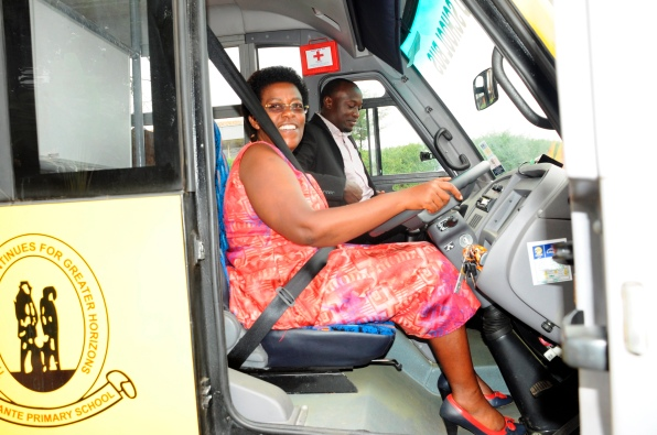 Florence Muhumuza Kyoshabire, the Supervisor Education Services at KCCA tries out the new Blue Band bus that Unilever Uganda handed over to Kitante Primary School. This was the grande prize of the puzzles challenge