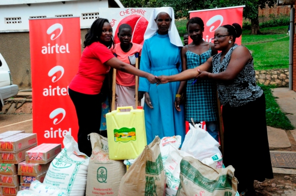 Airtel CSR manager Charity Rwabutomize hands over the donated items to Cheshire Homes Program Director Samalie Matovu