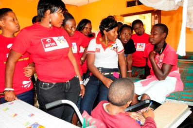 Airtel staff interract with one of the children at Katalemwa Cheshire Home for Rehabilitation Services. Airtel staff donated assorted items to the children