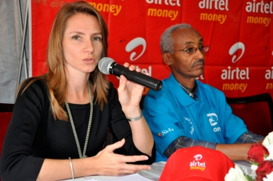 Grameen Foundation Mobile Financial Services Program Director Lisa Kienzle addressing the community. Right is Fikru Abebe Plan Uganda Country Director.