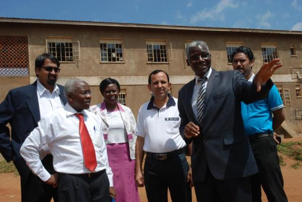 The Headteacher Kisugu Church of Uganda Primary School, James Juuko (2R) shows Manish Thappar (3R) the Bajaj Auto Head of Business for East Africa and other officials round the school.