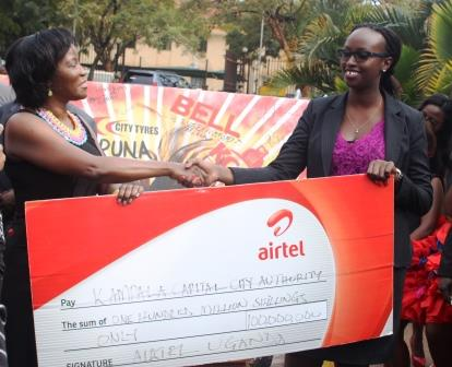 KCCA Executive Director Ms. Jennifer Musisi receives a cheque worth UGX100m from Airtel's Brand Assets and Properties Manager Noela Byuma