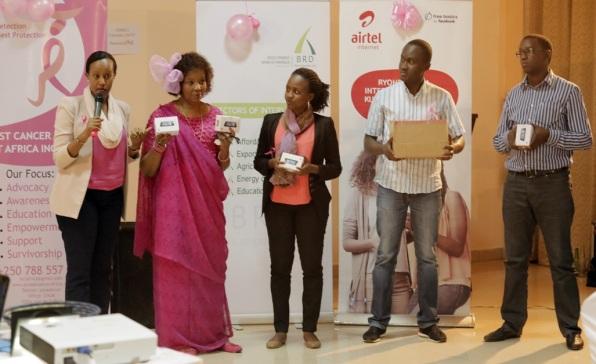 Airtel Rwanda Head of CSR & Corporate Communications, Denise Umunyana hands over handsets to help in Breast Cancer Awareness