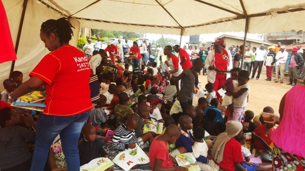 Airtel Rwanda staff members distributing books to children at the Reading Umuganda activity.