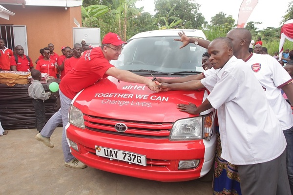 Airtel Uganda MD handing over the car to Mary Kabiito alongside her husband and son.