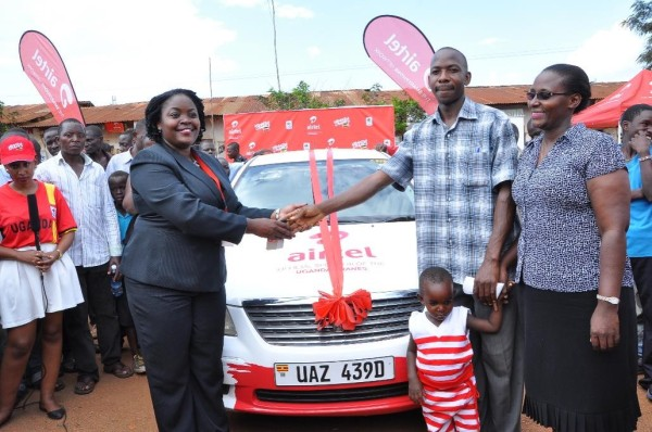 Kawooya Amiri Sunday the third car winner of Mujje Tulumbe  pomotion being congratulated by Airtel Uganda Head of Brand and Communications Remmie Kisakye as his family looks on.