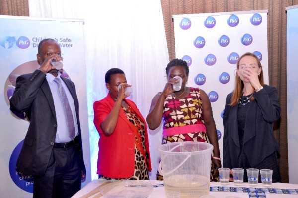 Commissioner of Water and Environmental Sector, Engineer Disan K Ssozi, Procter &Gamble CSDW Program Director, Ms Allison Tummon take water with the beneficaries during the P&G celebrati